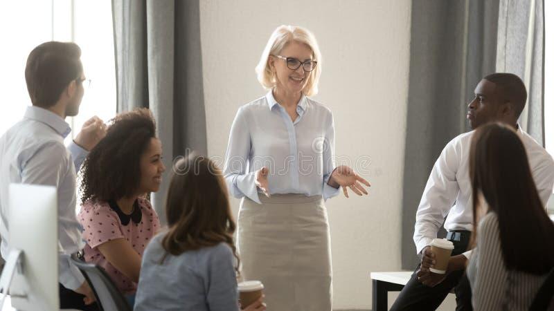 Treinador do mentor da mulher adulta que treina o grupo multicultural dos internos no escritório foto de stock