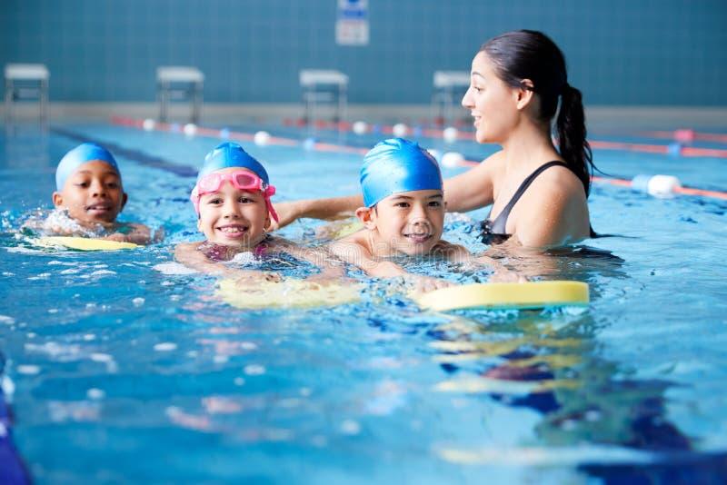 Treinador Do Setor Da Água Para Crianças Nadando Lição Em Pool Interior fotografia de stock
