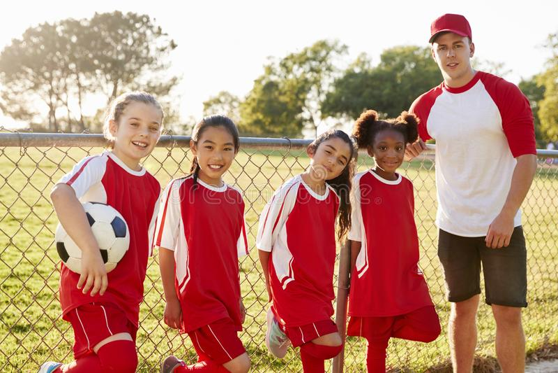 Treinador e moças em uma equipa de futebol que olha à câmera foto de stock