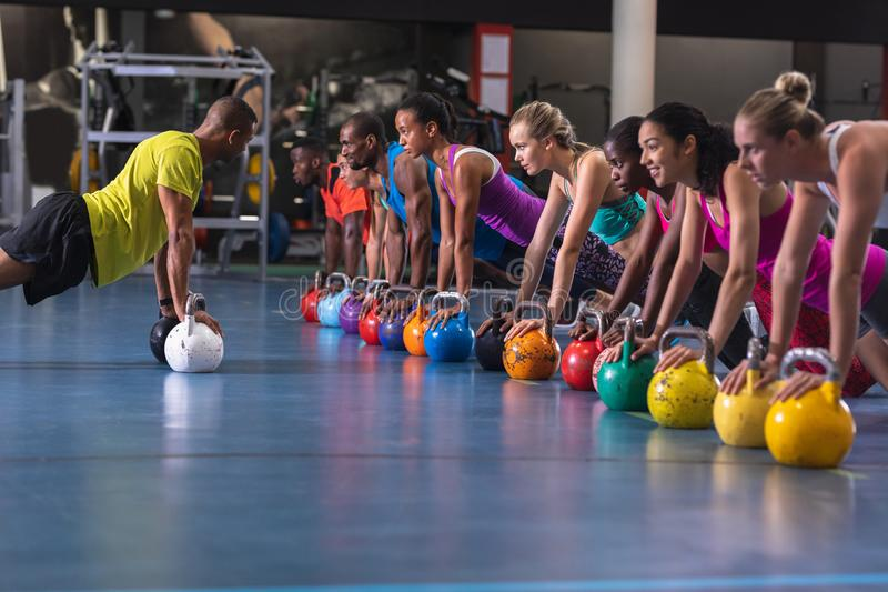 Treinador masculino treinando mulheres para se exercitar com kettlebell foto de stock royalty free
