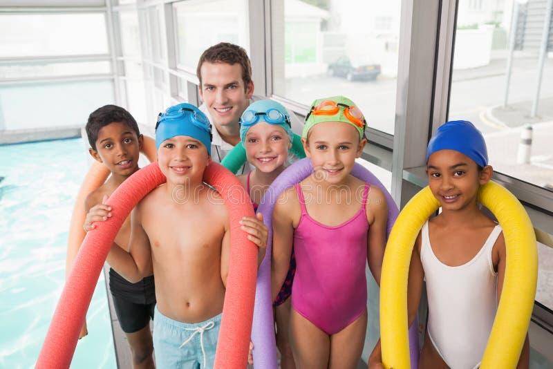 Treinador nadador com sua piscina dos estudantes fotografia de stock