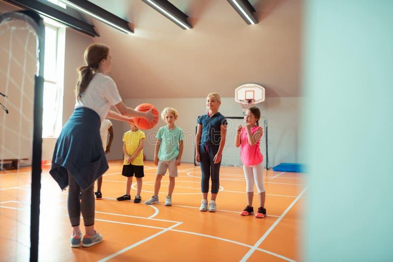 Treinador que ensina a seus alunos como jogar a bola imagem de stock
