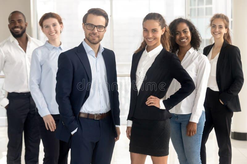Treinadores profissionais de sorriso dos líderes que olham a câmera com empresários dos empregados imagens de stock royalty free