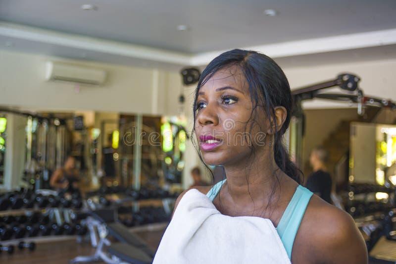 Treinamento afro-americano preto atrativo e cansado da mulher no clube de aptidão que mantém o suor da secagem de toalha esgotado foto de stock