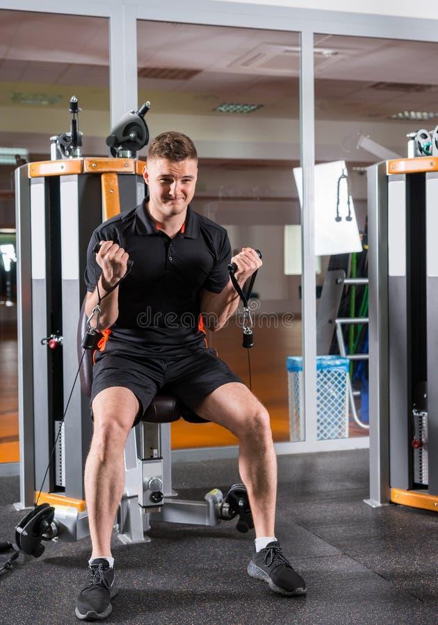 Treinamento apto do homem dos jovens na máquina moderna e dar certo no gym imagem de stock
