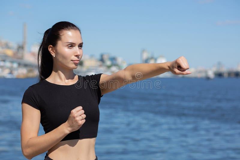 Treinamento atlético forte da menina a encaixotar perto do rio Espaço para o texto foto de stock