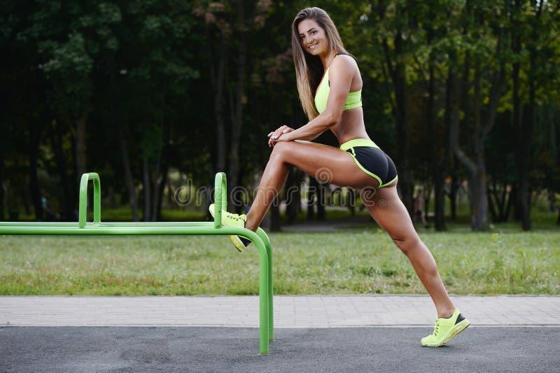Treinamento caucasiano novo muscular atlético forte bonito do exercício da mulher da aptidão do esporte exterior no gym na dieta  fotografia de stock