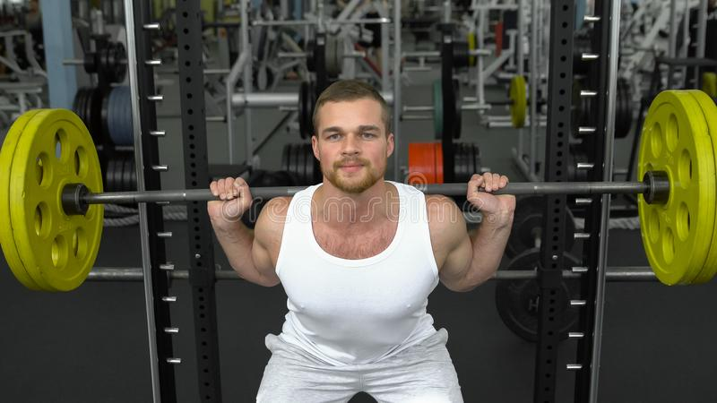 Treinamento da força no gym indivíduo no t-shirt que faz ocupas com um barbell halterofilista que faz o exercício com barbell imagens de stock