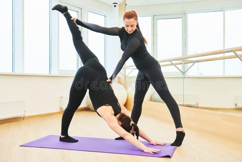 Treinamento da ioga Controles do instrutor da execução do exercício fotografia de stock