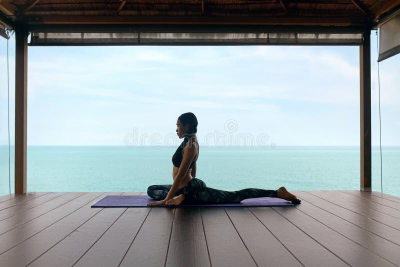 Treinamento da ioga A mulher no esporte veste o esticão do corpo perto do mar foto de stock royalty free