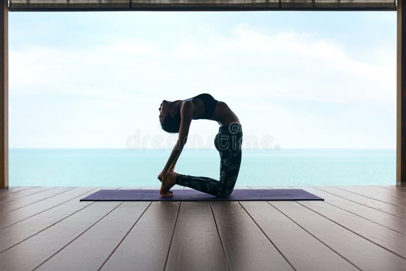 Treinamento da ioga A mulher no esporte veste o esticão do corpo perto do mar fotografia de stock