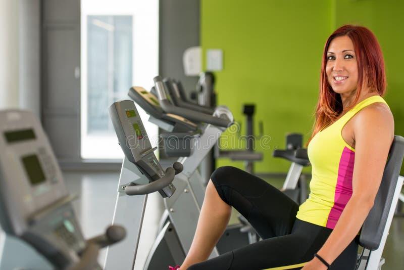 Treinamento da jovem mulher em uma bicicleta de exercício foto de stock royalty free