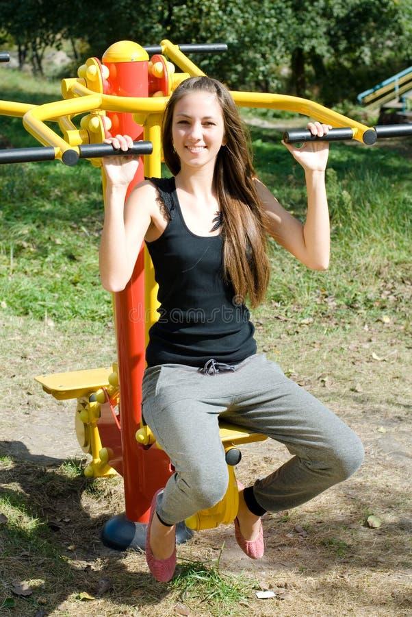 Treinamento da menina no construtor do músculo foto de stock