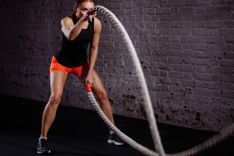 Treinamento da mulher com corda da batalha no gym apto da cruz fotografia de stock