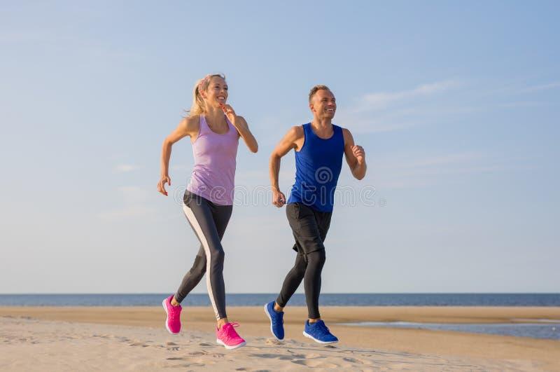 Treinamento de corrida dos pares da aptid?o dos corredores na praia imagens de stock