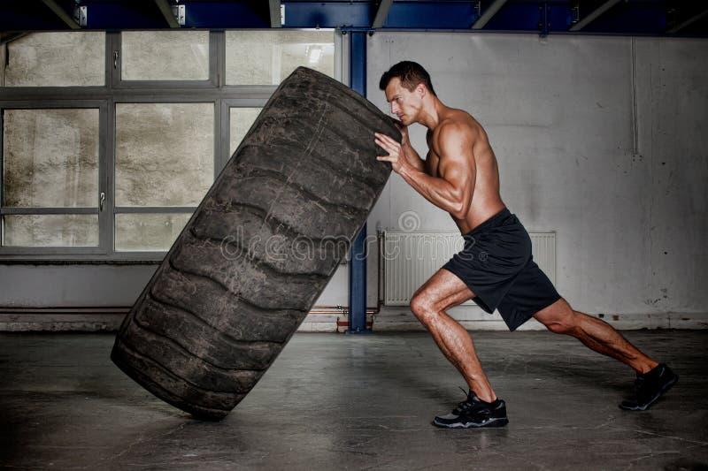 Treinamento de Crossfit - homem que lança o pneu imagens de stock