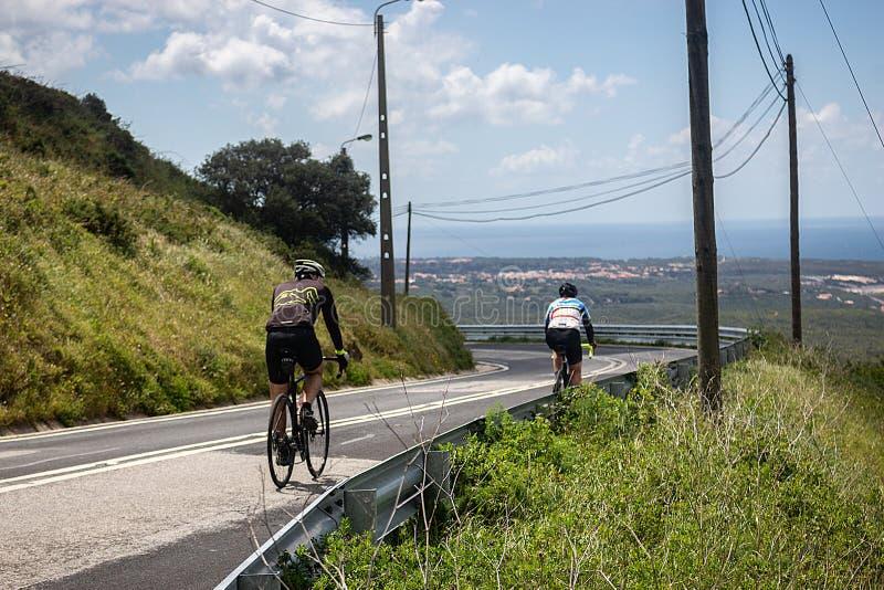Treinamento de dois ciclistas nas estradas dos cascais imagens de stock royalty free