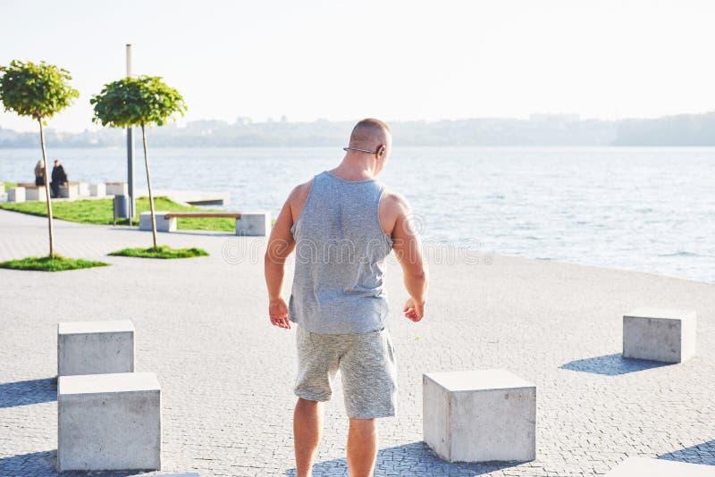 Treinamento do atleta do basculador e fazer exercício masculinos novos fora na cidade foto de stock