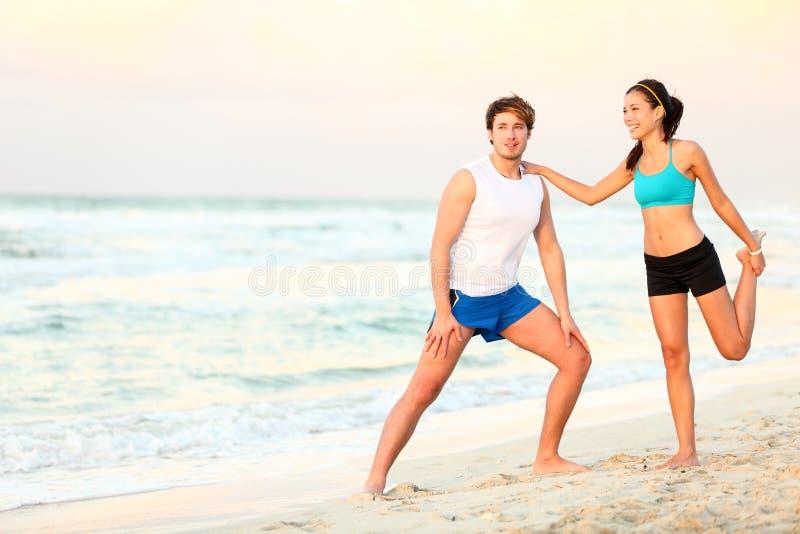 Treinamento do exercício dos pares na praia imagem de stock