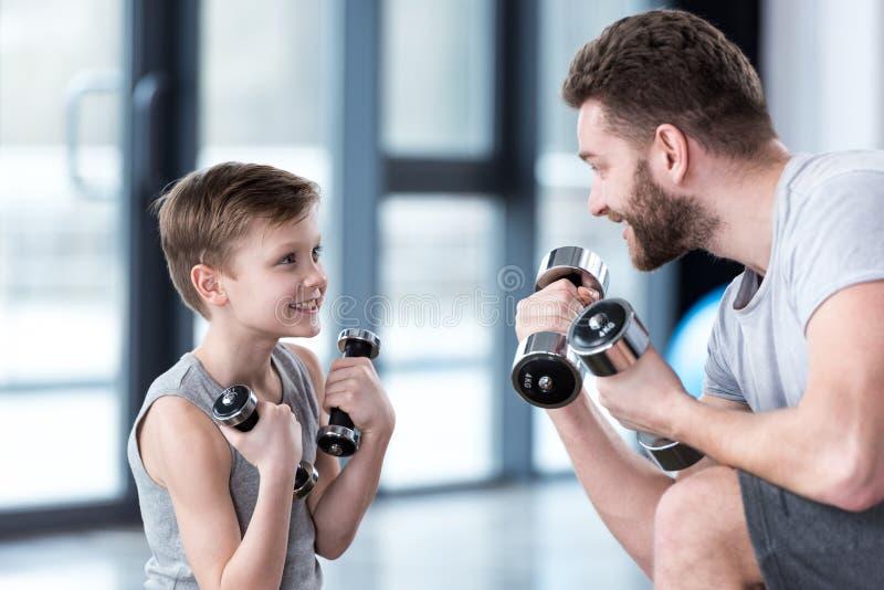 Treinamento do menino com pesos junto com o treinador fotos de stock royalty free