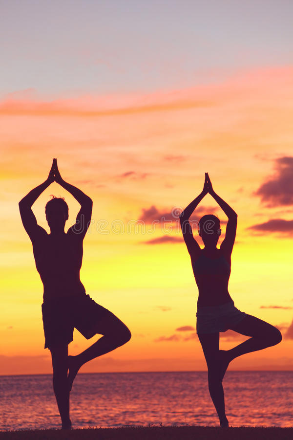 Treinamento dos pares da ioga no por do sol na pose da árvore imagens de stock royalty free