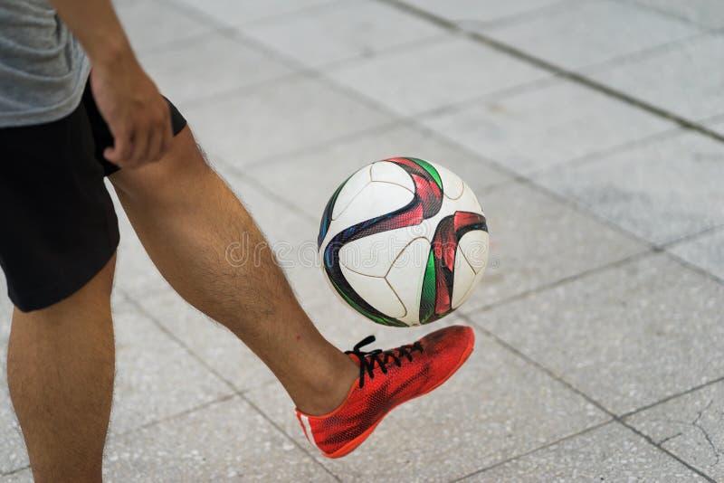 Treinamento exterior do futebol do close up com pés da bola e do menino fotos de stock royalty free