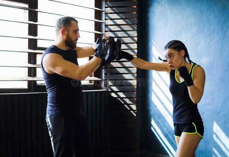 Treinamento fêmea branco apto do pugilista com o treinador do encaixotamento no gym fotografia de stock royalty free