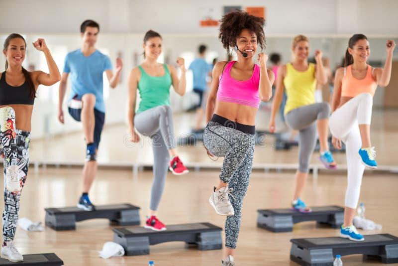 Treinamento fêmea do grupo da ligação do instrutor no fitness center imagens de stock royalty free