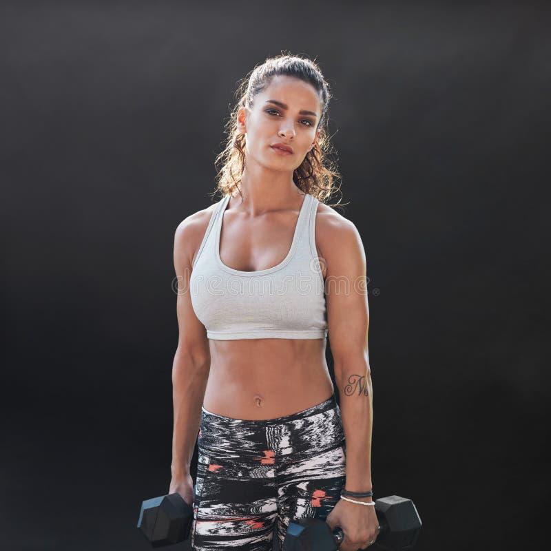 Treinamento fazendo fêmea forte e muscular do halterofilismo fotografia de stock royalty free
