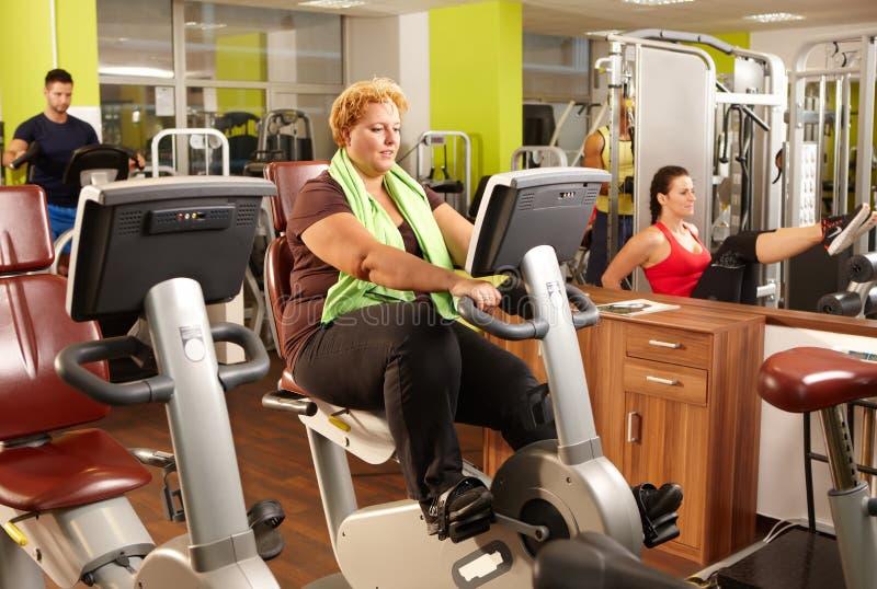 Treinamento gordo da mulher na bicicleta de exercício no gym imagem de stock
