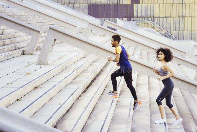 Treinamento interracial de casais correndo escadas imagem de stock royalty free