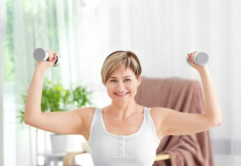 Treinamento maduro da mulher com pesos em casa fotografia de stock royalty free