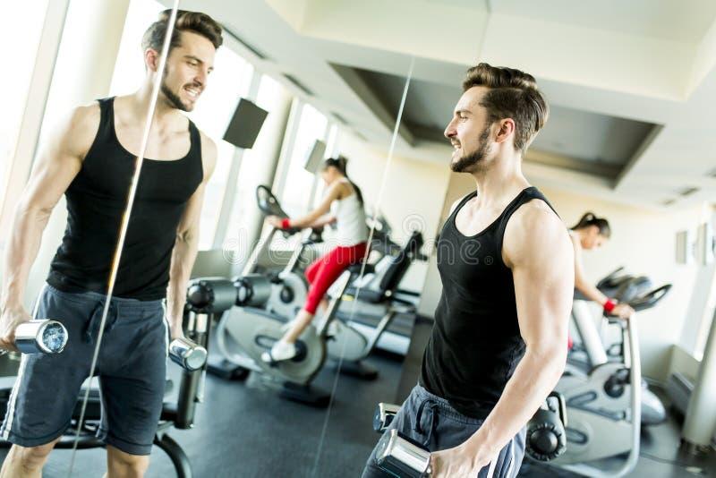 Treinamento muscular do homem com peso vermelho no gym imagem de stock