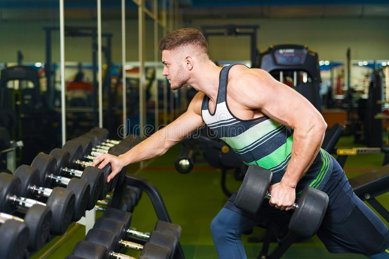 Treinamento muscular do homem no gym o indivíduo novo pegara um peso perto do espelho foto de stock royalty free