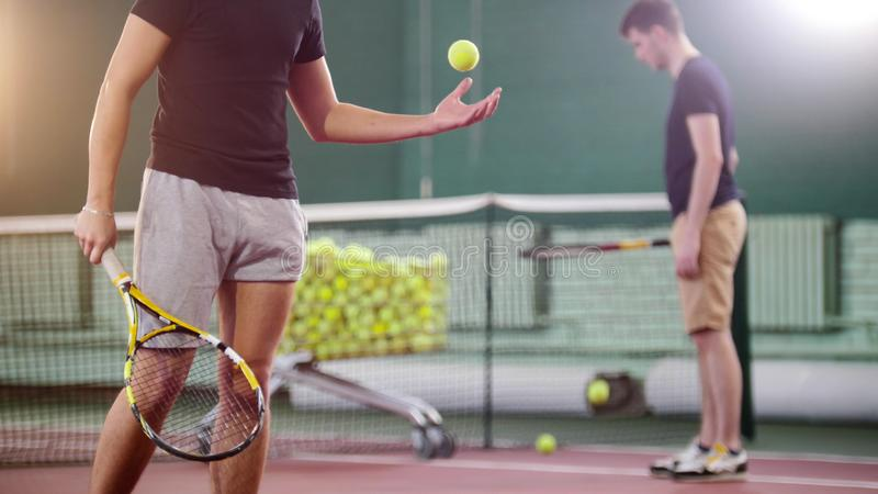 Treinamento no campo de tênis Homens novos que batem a bola do assoalho Um homem que joga acima uma bola de tênis foto de stock royalty free