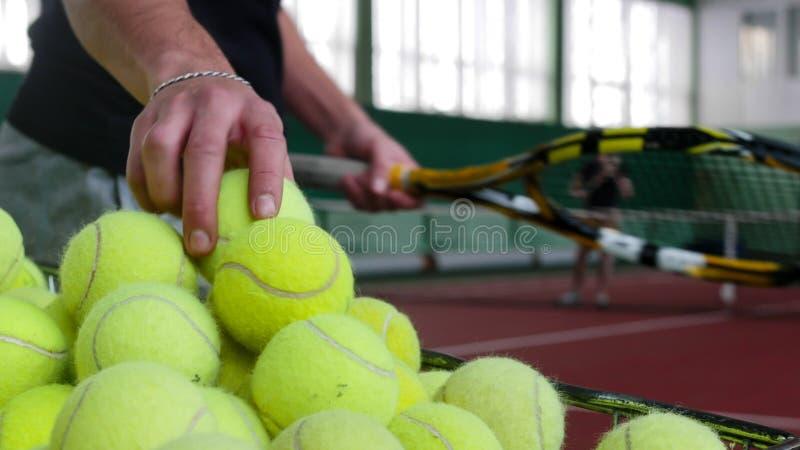 Treinamento no campo de tênis Um carro enchido com as bolas de tênis Um homem toma a bola do carro imagens de stock royalty free