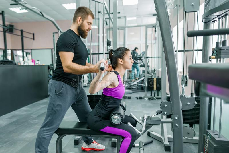 Treinamento pessoal do instrutor da aptidão e mulher de ajuda do cliente que fazem o exercício no gym Esporte, trabalhos de equip fotos de stock royalty free