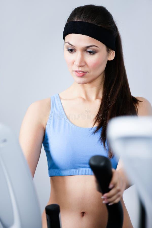 Treinamento Sportive da mulher no equipamento do gym no gym fotografia de stock