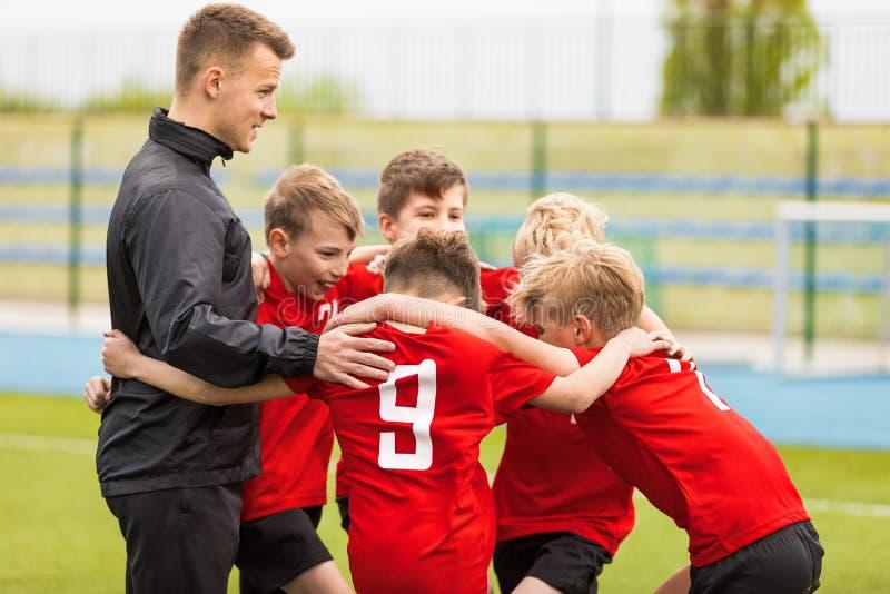Treinando esportes da juventude Futebol Team Huddle do futebol das crianças com treinador imagens de stock royalty free
