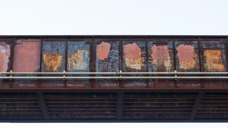 Treinbrug van ijzerrood wordt met roest en in verf wordt behandeld gemaakt die die omhoog graffiti behandelen die stock foto