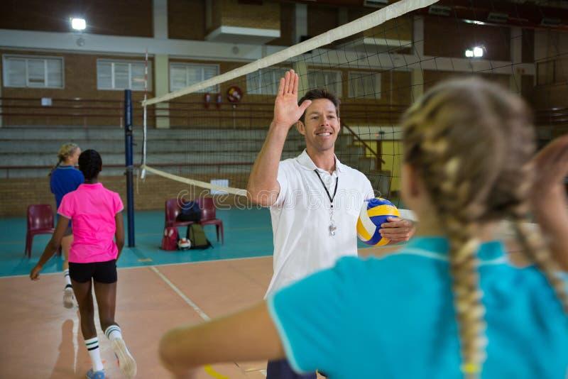 Treine a doação da elevação cinco ao jogador fêmea na corte de voleibol foto de stock royalty free