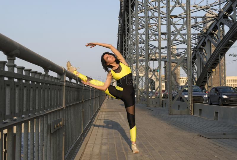treinen van 1 de witte sportenmeisje op een metaalbrug, een jonge vrouw in openlucht belast met sportenstad royalty-vrije stock afbeeldingen
