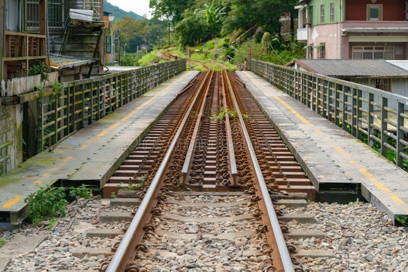 Treinspoor over brug die tot lokale stad leidt stock fotografie