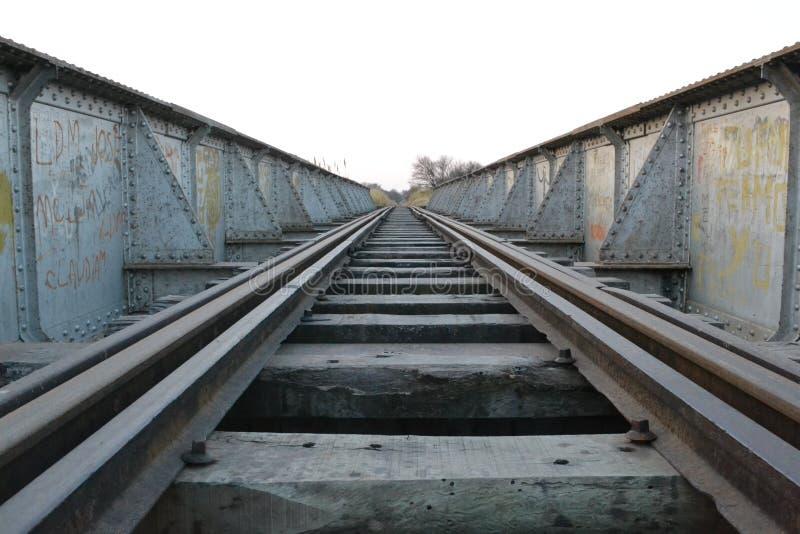 treinsporen die naar de metaal gekleurde horizon en zich over versleten hout verwijderen royalty-vrije stock afbeelding