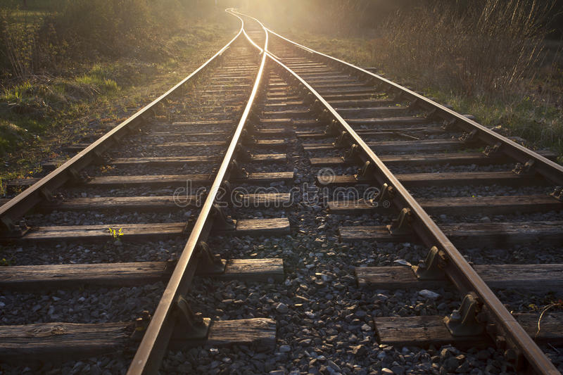 Treinsporen die tot de zonsondergang leiden stock fotografie