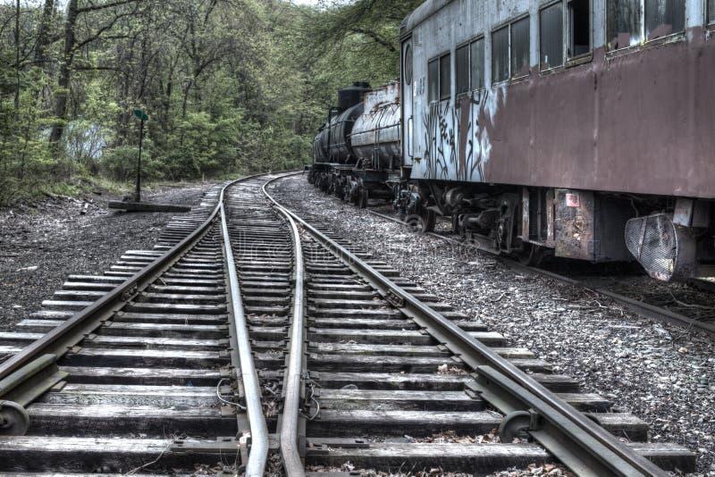 Treinsporen en verlaten treinauto stock foto