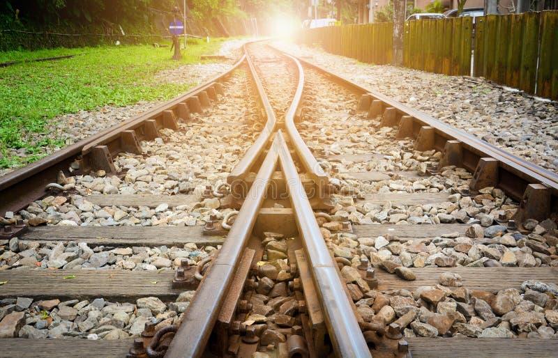 Treinsporen op grint, twee van spoorwegensporen voegen met zonsondergangachtergrond samen, concept succes stock foto
