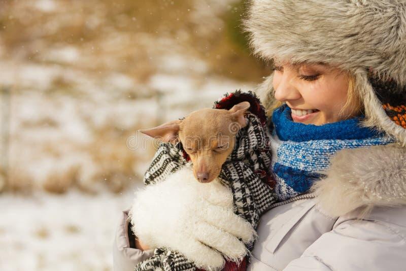 ?treinte de femme chauffant son petit chien en hiver photos libres de droits
