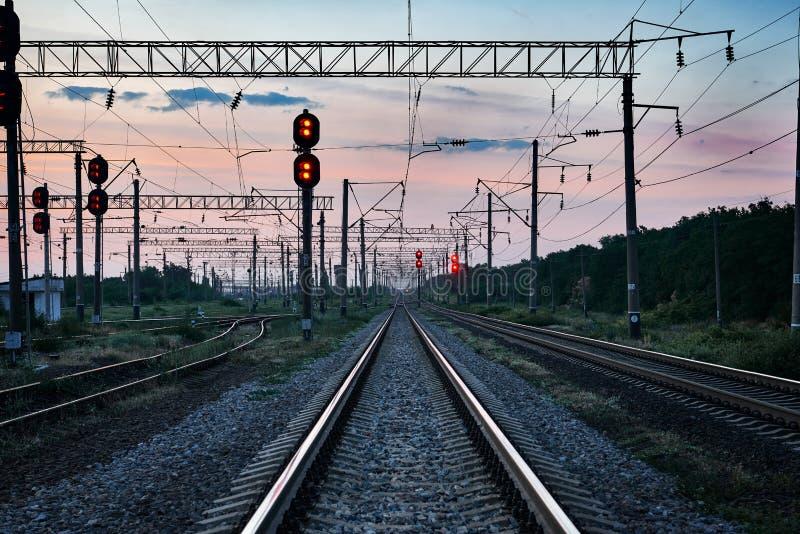 Treinverkeerlichten en infrastructuur tijdens mooie zonsondergang, kleurrijke hemel, vervoer en industrieel concept royalty-vrije stock afbeelding