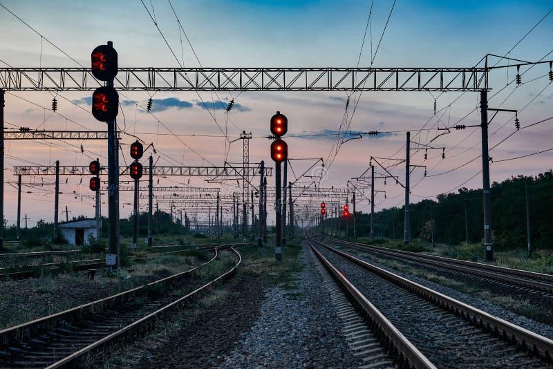 Treinverkeerlichten en infrastructuur tijdens mooie zonsondergang, kleurrijke hemel, vervoer en industrieel concept royalty-vrije stock foto